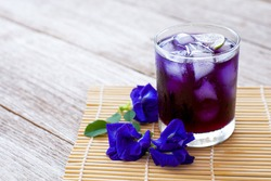 Butterfly pea or blue pea juice ice tea in glass and clitoria ternatea flowers isolated on wood table background. Copy space.