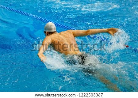 butterfly stroke male swimmer athlete swimming in pool #1222503367