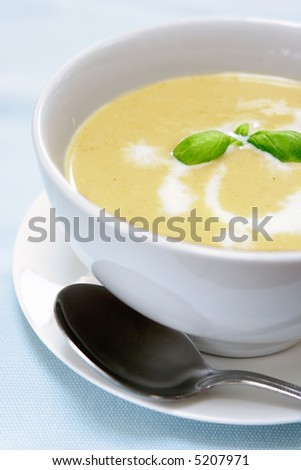 Butternut and potato soup served with cream and sprig of fresh basil.