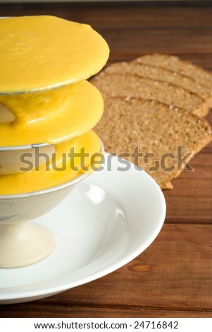 Butternut soup in bowl with rye bread in background