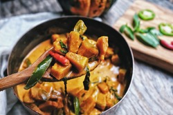 Butternut squash/ pumpkin in authentic Thai red curry coconut sauce with red and green chilies. Serve with grilled cashew nut in a butternut squash bowl. Selective focus at the wooden spoon.