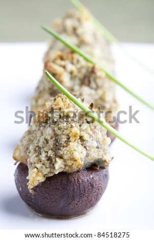 Button mushrooms stuffed with chopped nuts herbs and spices topped with a chive.