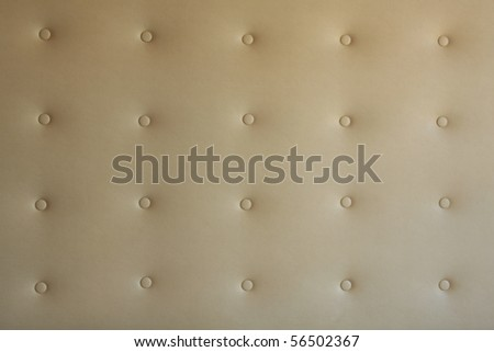 Buttoned beige leather background exposed to soft light