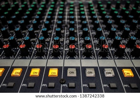 Buttons and knobs with slider in various parts of Sound mixer control panel or Audio mixer board console in the audio control room #1387242338