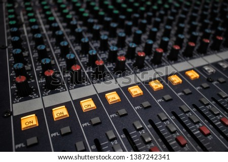 Buttons and knobs with slider in various parts of Sound mixer control panel or Audio mixer board console in the audio control room #1387242341
