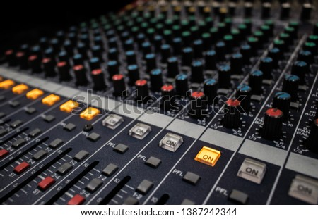 Buttons and knobs with slider in various parts of Sound mixer control panel or Audio mixer board console in the audio control room #1387242344