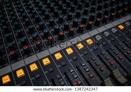 Buttons and knobs with slider in various parts of Sound mixer control panel or Audio mixer board console in the audio control room #1387242347