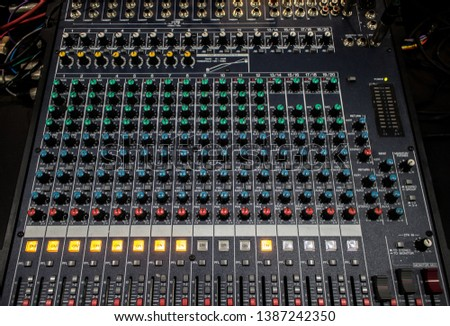 Buttons and knobs with slider in various parts of Sound mixer control panel or Audio mixer board console in the audio control room #1387242350