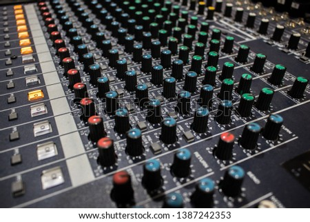 Buttons and knobs with slider in various parts of Sound mixer control panel or Audio mixer board console in the audio control room #1387242353
