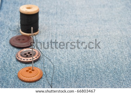 Buttons and needle on jeans