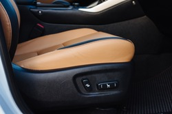 Buttons for adjusting seat position. Car interior. Close up of yellow leather car seat and position adjustment button.