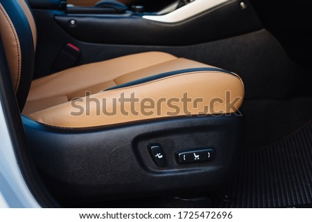 Buttons for adjusting seat position. Car interior. Close up of yellow leather car seat and position adjustment button. Foto stock ©
