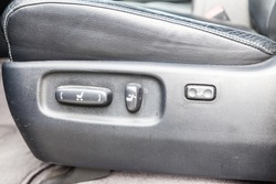 Buttons for adjusting the seat horizontally in height by tilting backrest with black leather upholstery in the car after cleaning and detailing in the vehicle repair workshop. Auto service industry.