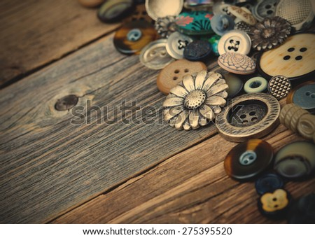buttons in large numbers scattered on aged wooden boards of old desk. Copy space. instagram image retro style