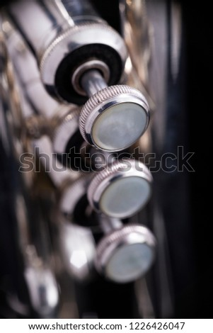 Buttons with grooves on valves of a silver plated trumpet on a black background