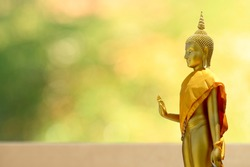 Buudha head and side body statue with green and yellow bokeh background as golden aura. Buddhism pray for faith and Asian religion.