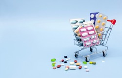Buy and shopping medicine concept. Various capsules, tablets and medicine in shop trolley on a blue background. Creative idea for health care, health insurance and pharmaceutical company. Copy space.