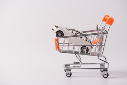 Buy new white car parking tax industry concept. Side profile close up photo of small mini toy car lying in shopping cart isolated over grey background with empty blank space