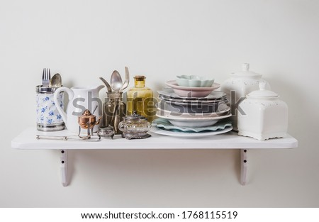 Buy old vintage romantic tableware in secondhand store concept. Pile of valuable old tableware on store shelf for kitchen.