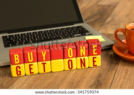 Buy One Get One written on a wooden cube in a office desk