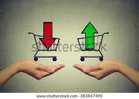 Buy or cell concept. Stock market trading. Two hands with consumer baskets with up and down arrow signs isolated on gray wall background
