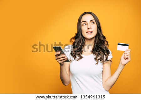 Buy or not to buy? Confused and thoughtful girl with a bank card and a phone in her hands is thinking over the thing she wants to buy and slightly biting her bottom lip.