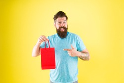Buy product. Gender differences in purchase decision making. Happy hipster hold paper bag. Bearded man smiling with fashion purchase. Impulse purchase. Shopping concept. Shop store mall boutique.