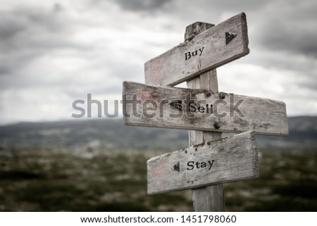 Buy, sell and stay text on wooden signpost outdoors. Marketing, stock, stocks and money concept.