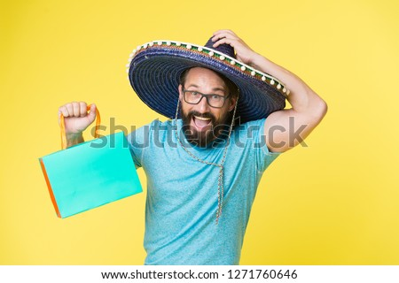 Buy souvenir from travel. Man wear sombrero hat shopping yellow background. Guy with beard happy in sombrero. Souvenir gift from abroad. Man hold shopping bag. Buy souvenir for friends and family.