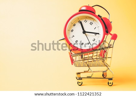 Buy time, Shopping cart with red vintage alarm clock show 10 O'clock over yellow background  Foto stock ©