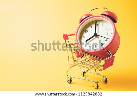 Buy time, Shopping cart with red vintage alarm clock show 8 O'clock over yellow background  Foto stock ©
