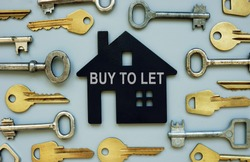 Buy to let concept. Lots of keys and a model of the house.