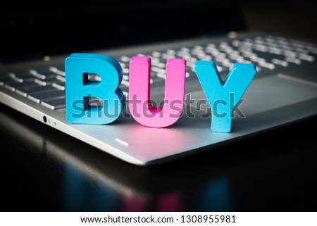 Buy word on laptop bottom at black background. Wooden colorful letters B, U, Y set on opened notebook. Concept of buying things in internet. Online shopping and e-commerce. Consumerism. Shopaholism