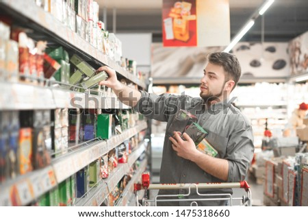 Buyer buys a discount product at a supermarket. Portrait of a man wearing a shirt, takes packets of tea from supermarket shelves.Man with a shopping cart takes a lot of tea packs in the grocery store #1475318660