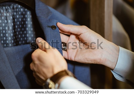 buyer holds the costume collar button and checks the cloth of expensive clothes in the clothing store