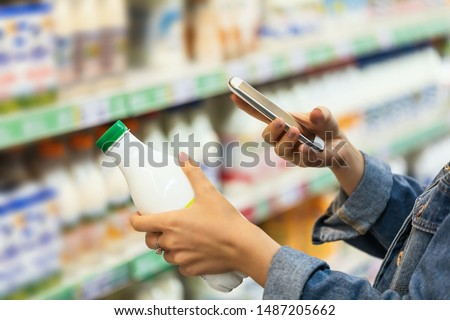 Buyer photographs a bottle of milk, a mystery shopper. Checking the quality of the goods by barcode, closeup
