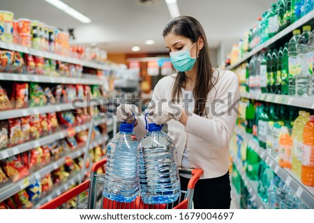 Buyer wearing a protective mask.Shopping during the pandemic.Emergency to buy list.Water supplies shortage.Panic buying during coronavirus outbreak.Preparation for a pandemic quarantine
