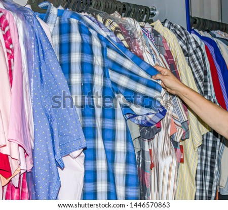 Buyers choose clothes. Female clothes on hangers and shelves in a clothing store. Casual clothes for girls and children. Fashionable style. Boutique in the mall. Discounts and sale.
