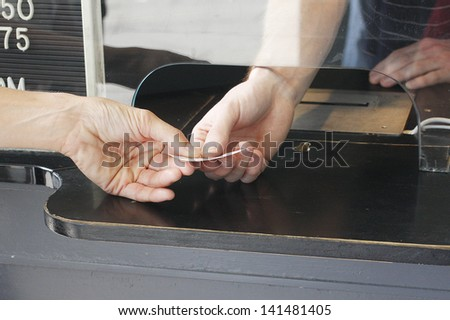 Buying a ticket at a  ticket booth.