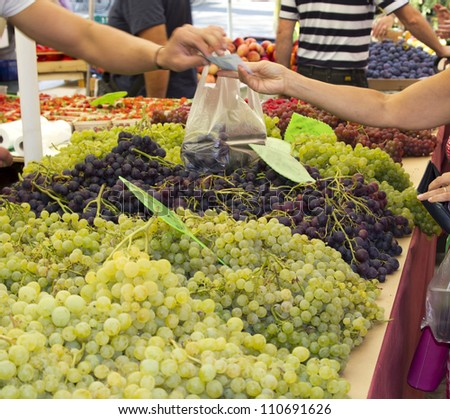 Buying and paying fresh organic grapes on sunny Mediterranean market