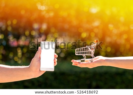 Buying and shopping online concept. a man and a  woman hands hold a basket and touch screen smart phone in the public park.
