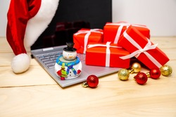 Buying Christmas gifts with laptop. Happy new year. Winter holidays sales. Online purchase bonus. Digital tablet at Christmas time. Festive surfing and shopping with a credit card on Xmas season.