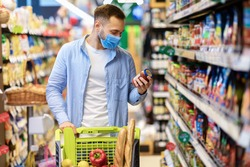 Buying Food. Portrait of young man wearing medical face mask shopping groceries in hypermarket, standing with trolley cart full of products in shop indoors, holding glass jar of sauce, checking label