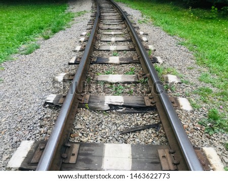 Buying iron rail railroad track thin long old nostalgia wonderful different angles perspectives background image of railroad crossing between green trees. #1463622773