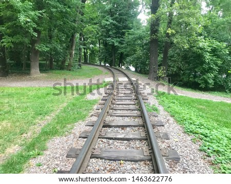 Buying iron rail railroad track thin long old nostalgia wonderful different angles perspectives background image of railroad crossing between green trees. #1463622776