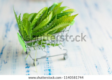 Buying, selling hemp. A shopping trolley with cannabis leaves on a wooden background.