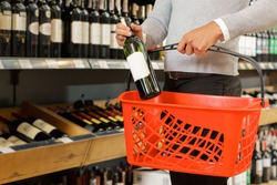 Buying some drinks. Photo of a man standing in a supermarket holding a shopping cart and putting a bottle of wine inside, wine shelves on the background