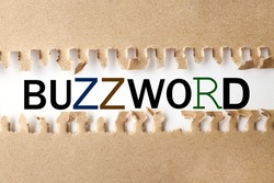 BUZZWORD. text on white paper over torn paper background.