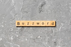 BUZZWORD word written on wood block. BUZZWORD text on cement table for your desing, concept.