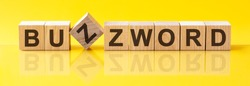 BUZZWORD word written on wood block. sales word is made of wooden building blocks lying on the yellow table. BUZZWORD, business concept, yellow background